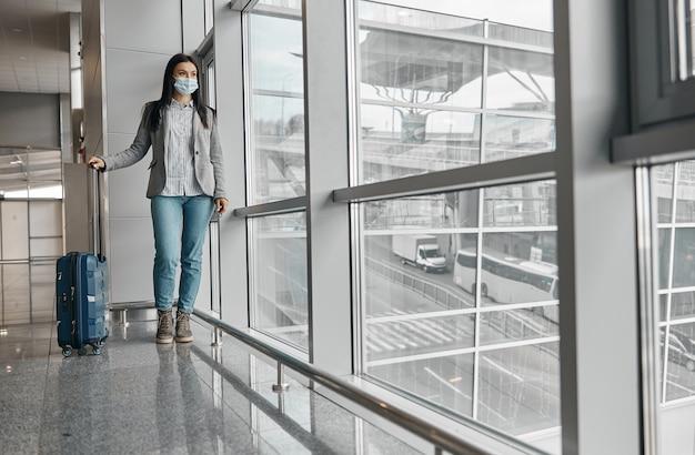 Nuovo ordine negli aeroporti. donna in maschera nel terminal con bagagli vicino a finestre panoramiche da sola
