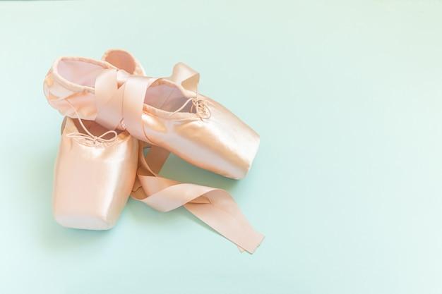 Nuove ballerine beige pastello con nastro di raso isolato su sfondo blu.