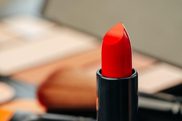 Nuovo rossetto rosso sul tavolo da trucco si chiuda