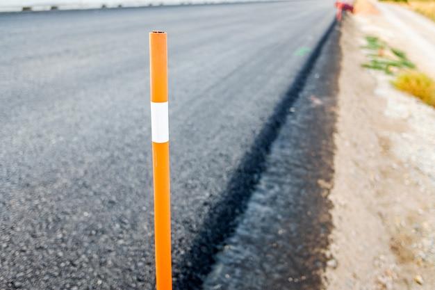 Lavori di costruzione di nuove strade, pali di sicurezza e asfalto fuori fuoco.