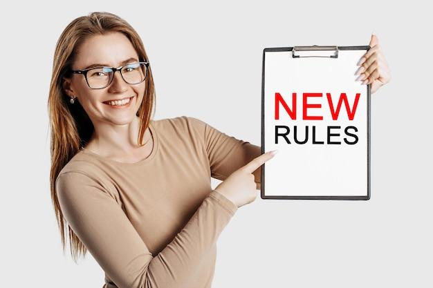 Nuove regole. la bella giovane donna di affari che indossa gli occhiali tiene una lavagna per appunti con finto spazio isolato su sfondo grigio