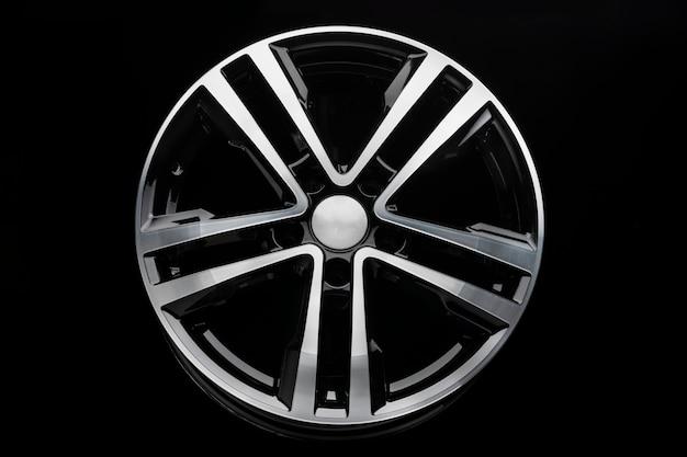 Nuovo cerchio in lega lucida, colore nero con frontale argento. parete scura, vista frontale.