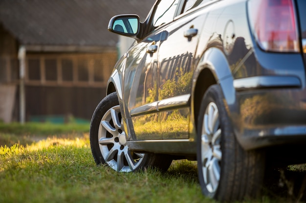Nuova automobile grigia lucida parcheggiata sull'erba verde su fondo rurale di estate soleggiata vaga