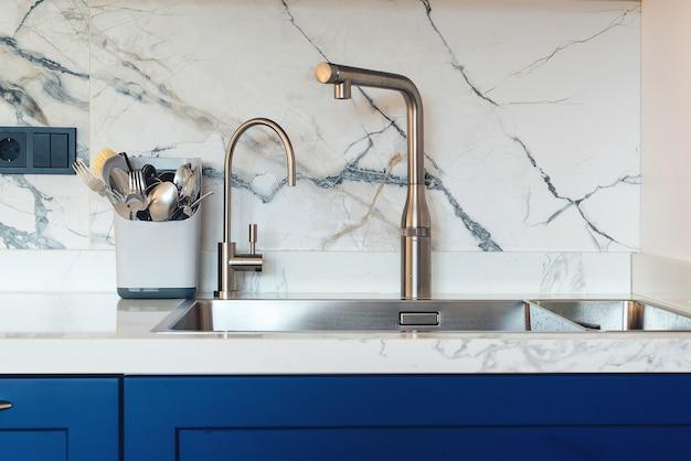 Nuovo lavello e rubinetto moderno in cucina elegante. nuova cucina di lusso con alzatina piastrellata in marmo. interiore della cucina moderna. lavandino da cucina pulito, primo piano.