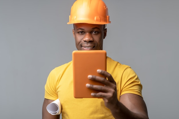 Nuove tecnologie. attraente giovane afroamericano sorridente in casco costruzione arancione con tablet in mano su sfondo chiaro