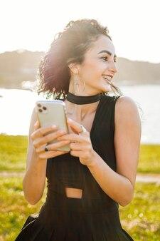 Nuova generazione femminile dipendente dalla tecnologia z con il telefono in mano sorridente