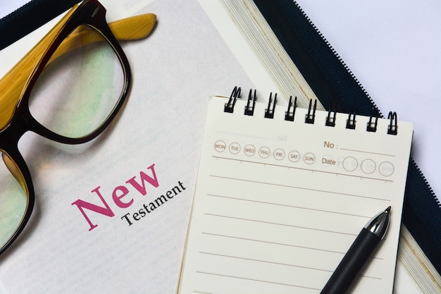 Copertina del nuovo testamento nella sacra bibbia con taccuino, penna e occhiali
