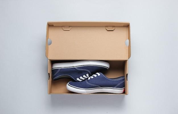 Nuove sneaker alla moda in una scatola di cartone su superficie grigia.