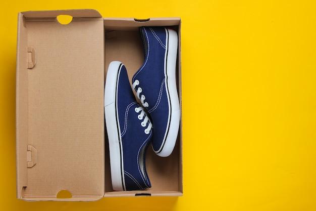 Nuove sneaker alla moda in scatola di cartone sulla superficie gialla.