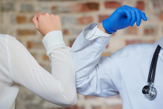Un nuovo modo di salutare per evitare la diffusione del coronavirus. un dottore e una femmina si piegano sui gomiti invece di salutare con un abbraccio o una stretta di mano contro un muro di mattoni
