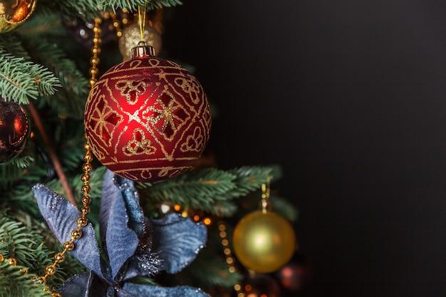 Capodanno 2020. buon natale buone feste. natale classico decorato albero di capodanno con decorazioni di ornamento d'oro giocattolo e palla. moderno appartamento di design d'interni in stile classico nero scuro