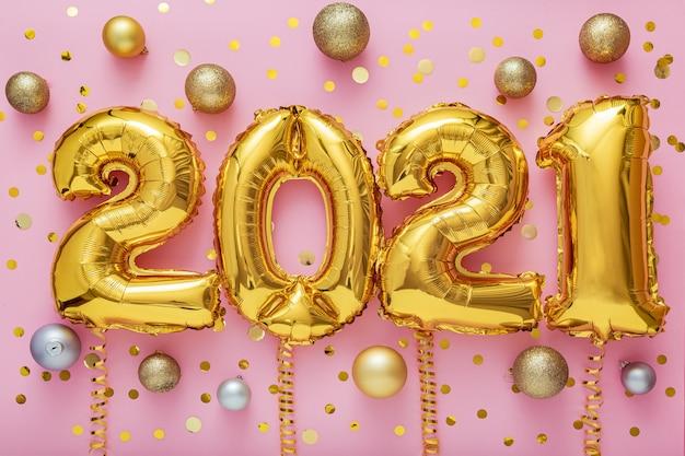 Numeri d'oro della mongolfiera del nuovo anno 2021 su rosa con decorazioni festive di palline di coriandoli dorati.