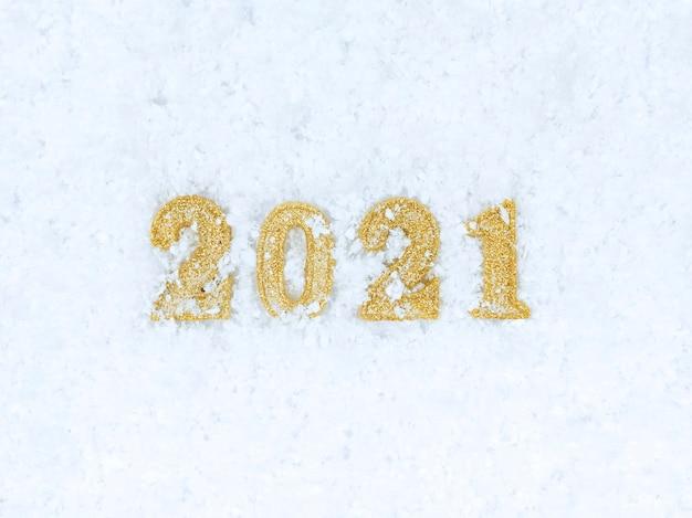 Figure del nuovo anno 2021 su una priorità bassa bianca di struttura della neve.