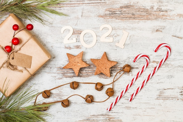 Saluto del nuovo anno 2021 con bastoncini di zucchero e ornamenti natalizi su un tavolo di legno bianco