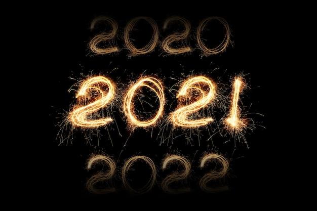 Anno nuovo 2021 luce di scintille. le stelle filanti disegnano figure 2021. luci e lettera del bengala. elenco delle cifre dell'anno