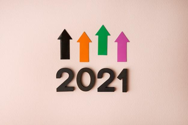 Nuovo anno 2021 con frecce sulla superficie rosa