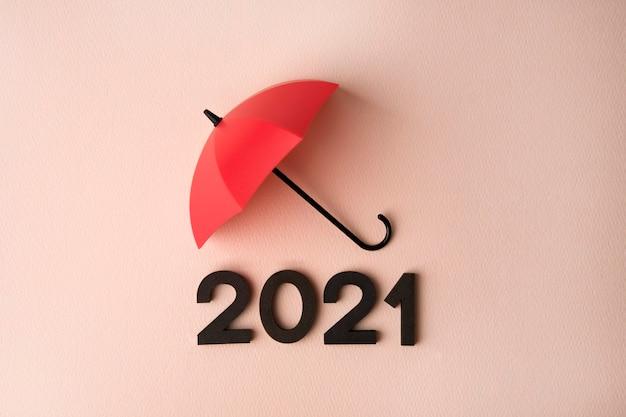 Nuovo anno 2021 con l'ombrello rosso sulla superficie rosa