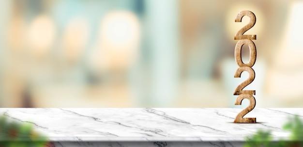 Rendering 3d del nuovo anno 2022 sul tavolo di marmo bianco a sfocatura dello sfondo chiaro del bokeh astratto