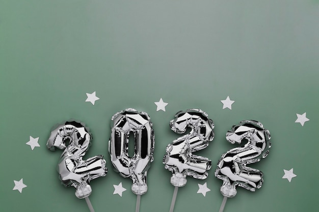 Capodanno 2022 o natale sfondo verde laici piatta. vista dall'alto su palloncini 2022 argento o numeri metallici su bastoncini con stelle. invito o concetto di biglietto di auguri. atmosfera festosa. foto di alta qualità