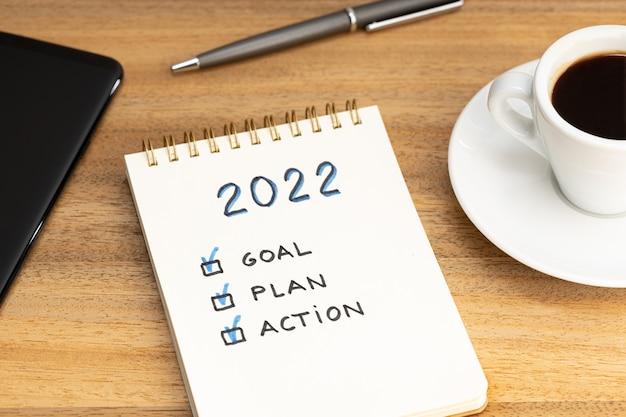 Obiettivo del nuovo anno 2022, piano, testo dell'azione su blocco note e tazza di caffè e smartphone sulla scrivania in legno. concetto di motivazione aziendale