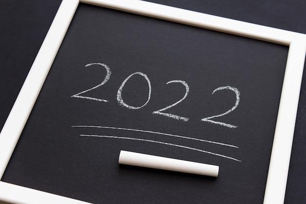 Numeri del nuovo anno 2022 scritti in gesso bianco su carta nera opaca in cornice bianca Foto Premium