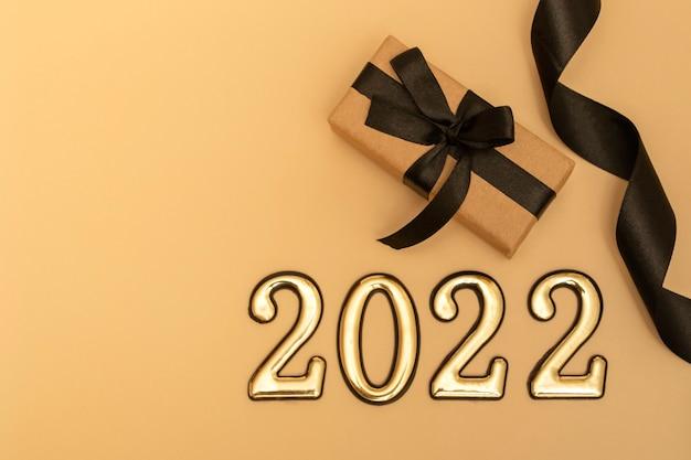 Nuovo anno 2022. mockup di capodanno vista dall'alto su sfondo beige: nastro nero, confezione regalo, numeri dorati e scintillii multicolori. layout di cartoline, inviti.