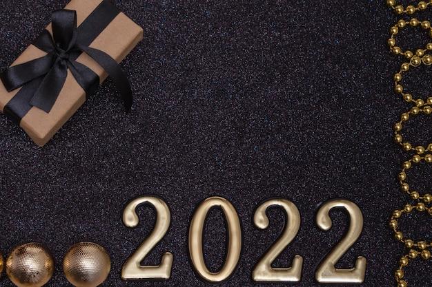 Nuovo anno 2022. mockup di capodanno vista dall'alto su sfondo nero lucido: nastro rosso, confezione regalo, numeri dorati e scintillii multicolori. layout di cartoline, inviti.