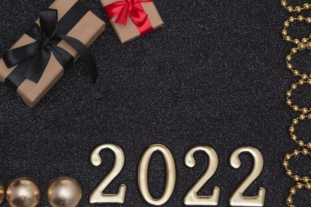 Nuovo anno 2022. mockup di capodanno vista dall'alto su sfondo nero lucido: nastro rosso, confezione regalo, numeri dorati e scintillii multicolori. layout di cartoline.