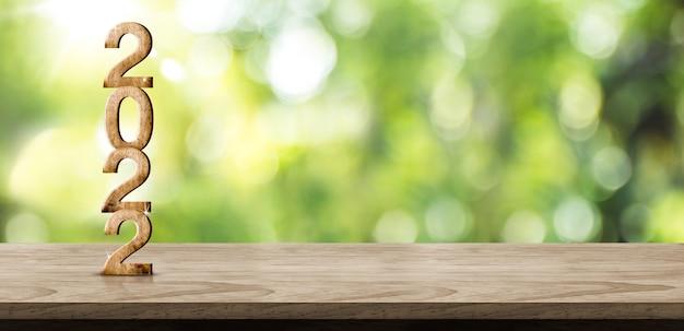Numero di legno del nuovo anno 2022 (rendering 3d) su tavola di legno a sfocatura sfondo astratto verde albero giardino bokeh, mock up spazio banner per la visualizzazione del prodotto o design. sfondo vacanza ecologica