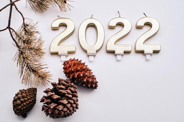 Il nuovo anno 2022 scritto con candele, pacchetti regalo e pigne essiccate su sfondo bianco