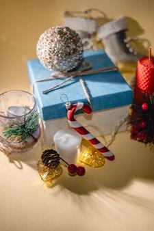 Atmosfera di capodanno candela regalo di capodanno e ghirlanda di giocattoli di natale su sfondo giallo