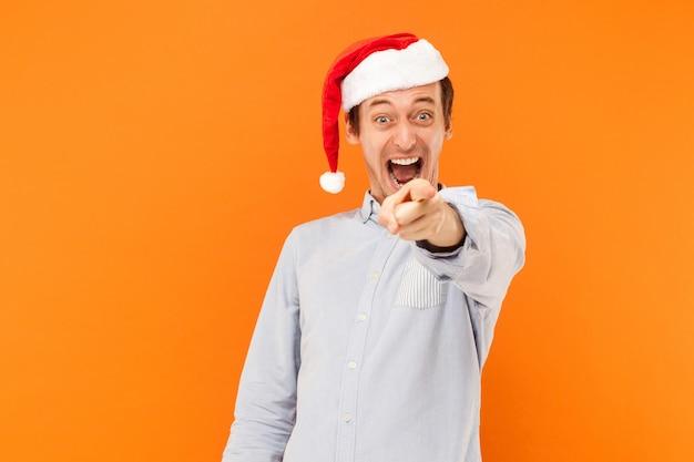 Uomo attraente del nuovo anno che punta il dito alla macchina fotografica e sorridente a trentadue denti si concentra sul viso