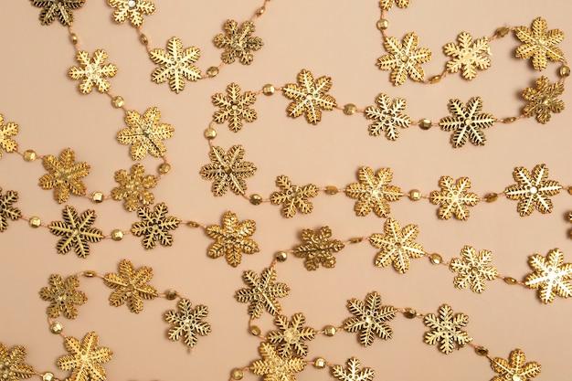 Sfondo del nuovo anno. su uno sfondo beige, una ghirlanda di fiocchi di neve dorati. modello di imballaggio vista dall'alto.