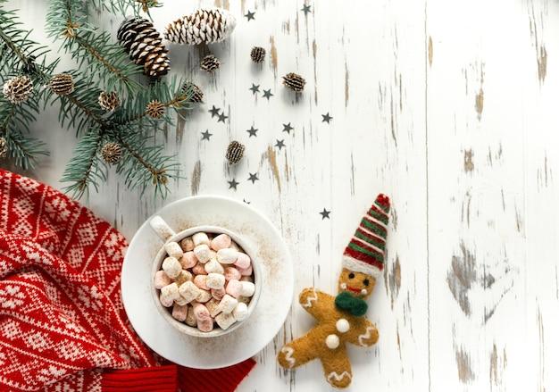 Sfondo di capodanno. una tazza di cacao con marshmallow, pan di zenzero, un ramo di un albero di natale con coni, un maglione rosso su uno sfondo di legno bianco con spazio di copia. layout piatto