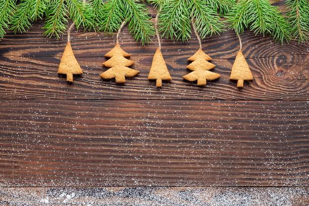 Sfondo di capodanno con biscotti a forma di albero fatti in casa appesi a rami di abete rosso