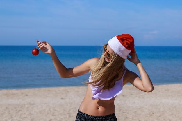 Capodanno sulla spiaggia ragazza divertente in un cappello da babbo natale con un albero di natale giocattolo nelle sue mani decorazioni di festa