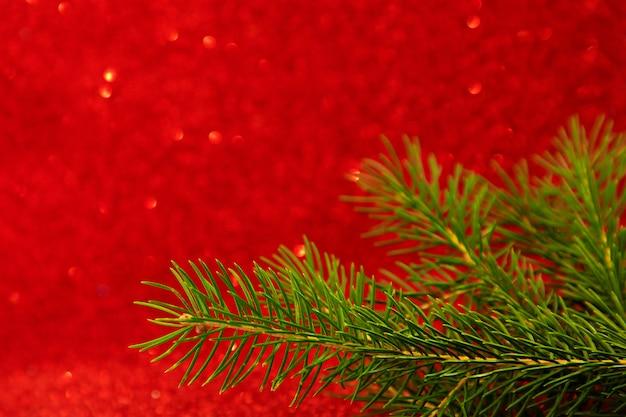 Carta di capodanno su sfondo rosso con bokeh ramo di albero di natale