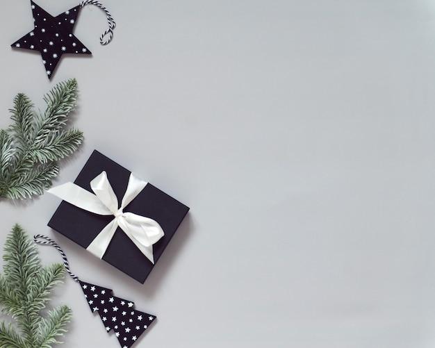 Celebrazione del nuovo anno piatta con scatola regalo e rami di albero di natale sfondo grigio