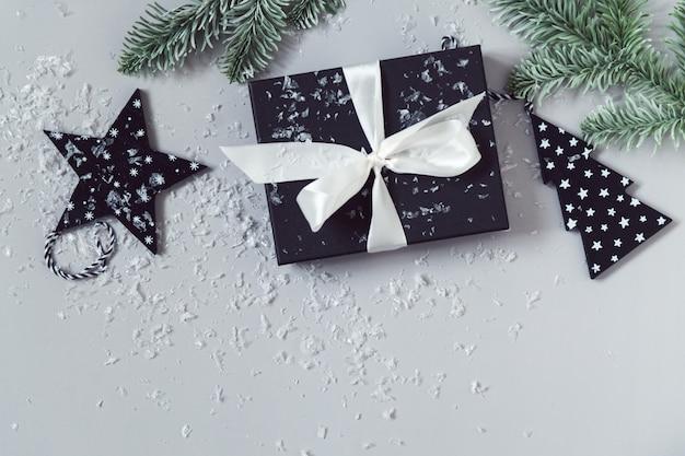 Celebrazione del nuovo anno piatta con scatola regalo neve e rami di albero di natale sfondo grigio