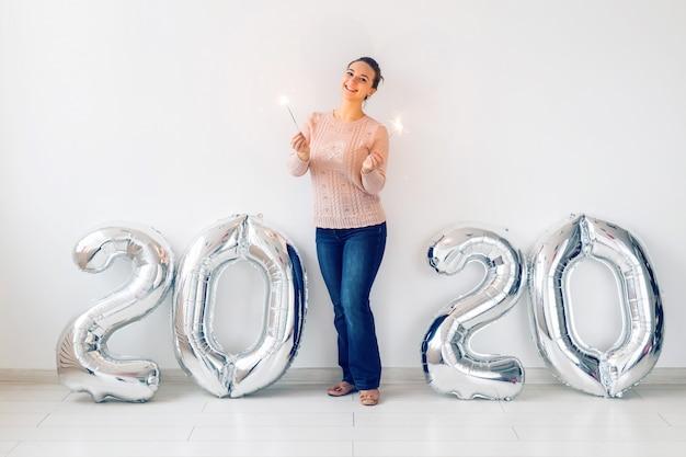 Celebrazione di nuovo anno e concetto del partito - la giovane donna felice con le stelle filante si avvicina ai palloni d'argento 2020.