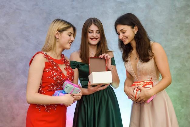 Celebrazione del nuovo anno. tre ragazze con scatole regalo in posa alla festa di capodanno
