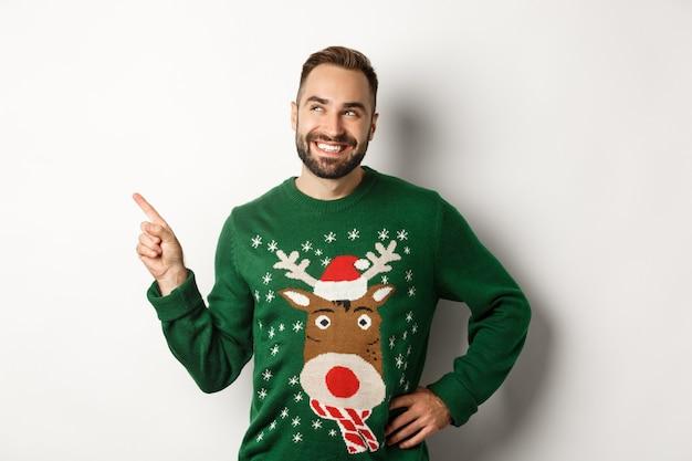 Celebrazione del nuovo anno e concetto di vacanze invernali. un bell'uomo sorridente con un maglione natalizio verde, che indica e guarda il negozio di logo nell'angolo in alto a sinistra, sfondo bianco.