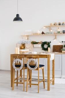 Capodanno e natale. festosa cucina scandinava nelle decorazioni natalizie. candele, rami di abete, supporti in legno, tavolo.