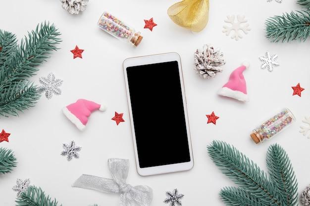 Piatto di natale di capodanno giaceva con telefono mock up, stelle, fiocchi di neve e decorazioni festive su sfondo bianco