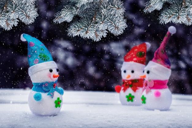 Biglietto di auguri di capodanno e natale con pupazzi di neve vicino a un abete rosso coperto di neve durante una nevicata
