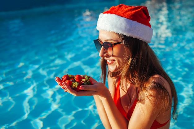 Vacanze di capodanno e natale. donna in cappello e bikini di santa che mangia le fragole nella piscina. vacanza tropicale