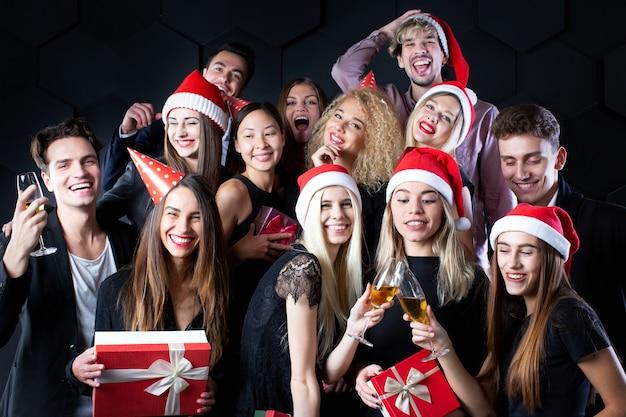 Capodanno e natale, persone allegre in cappelli di babbo natale e con regali celebrano la festa. gruppo di amici in abiti classici neri su sfondo nero divertirsi.