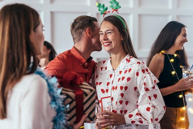 Anno nuovo, natale, l'uomo dice qualcosa all'orecchio della sua ragazza o la bacia su una guancia
