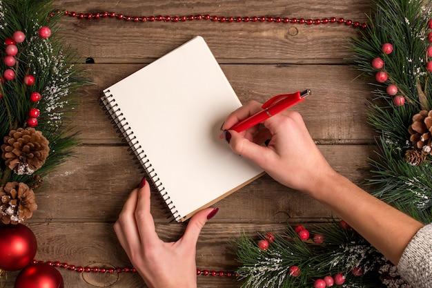 Mokcup di capodanno e natale. scrittura a mano su un notebook con luci di natale su sfondo di legno, spazio per il testo, copyspace. da sopra. concetto di pianificazione delle vacanze invernali. stile piatto.