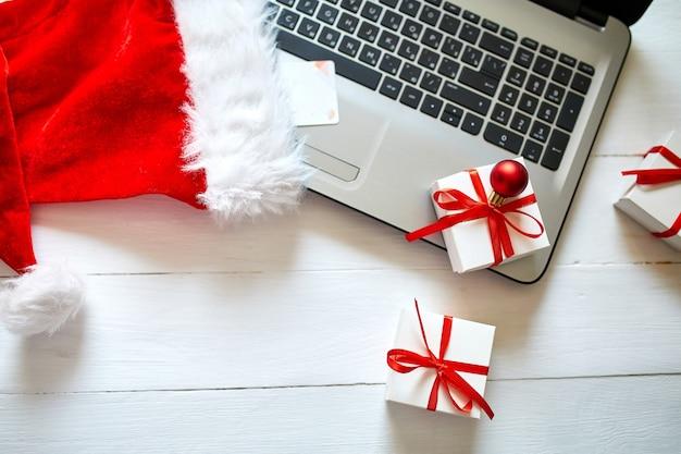 Acquisti online di capodanno e natale a casa, concetto di quaranina, notebook, carta di credito, cappello da babbo natale e confezione regalo su fondo di legno bianco, vista dall'alto, spazio di copia